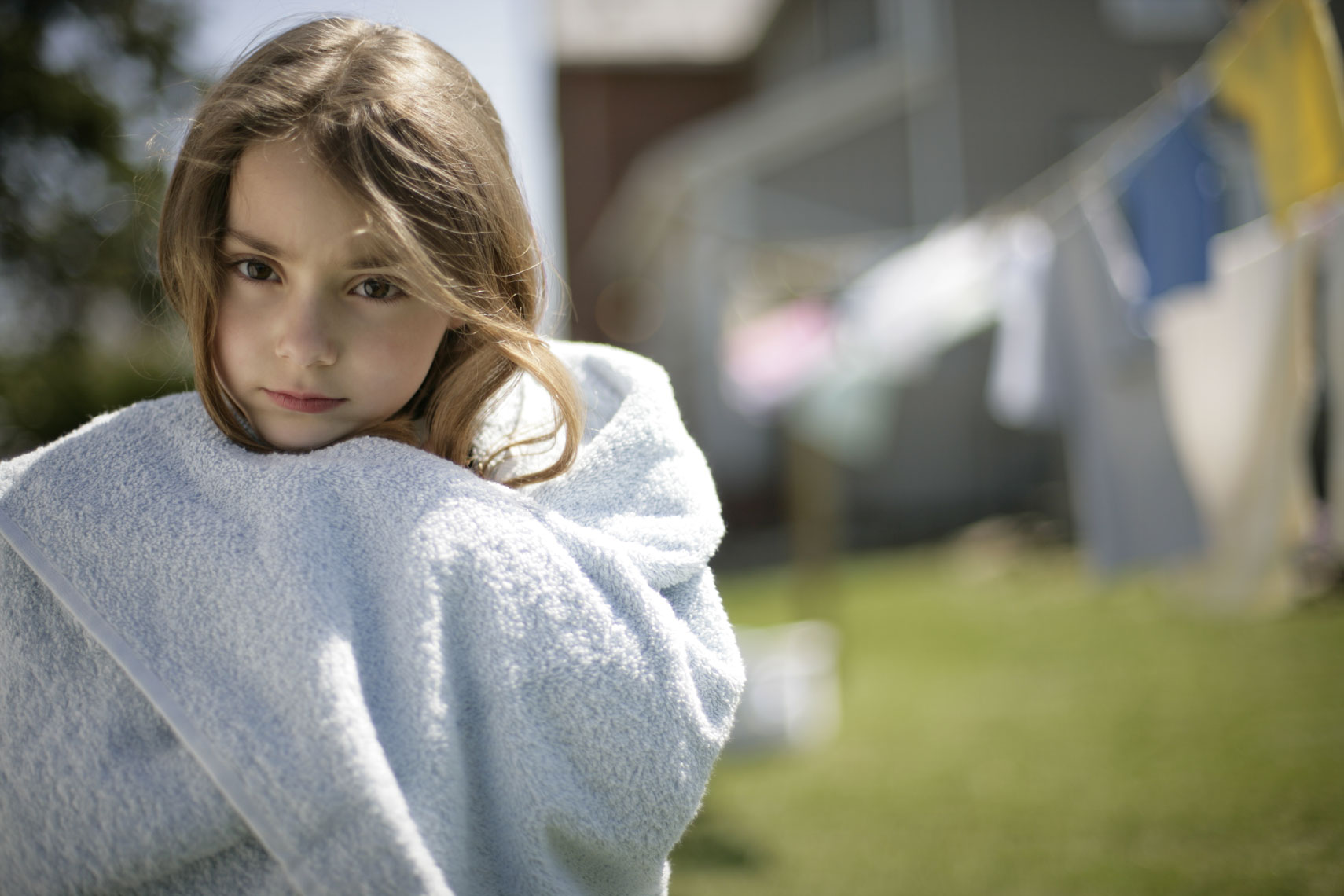 Pharmaceutical advertising portrait of a young girl wrapped in a towel outside