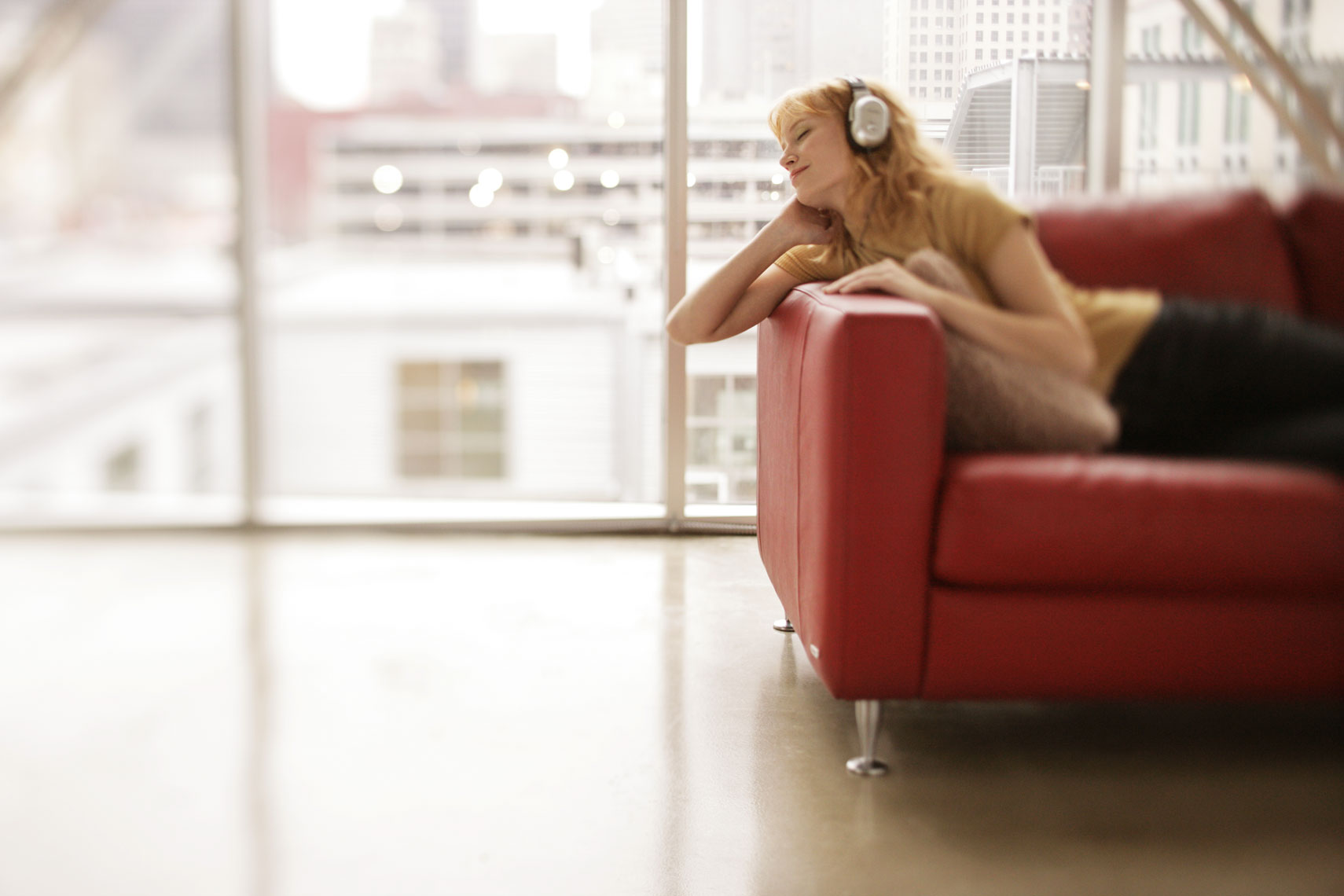 Lifestyle Portrait Of Woman Listening To Headphones In Loft