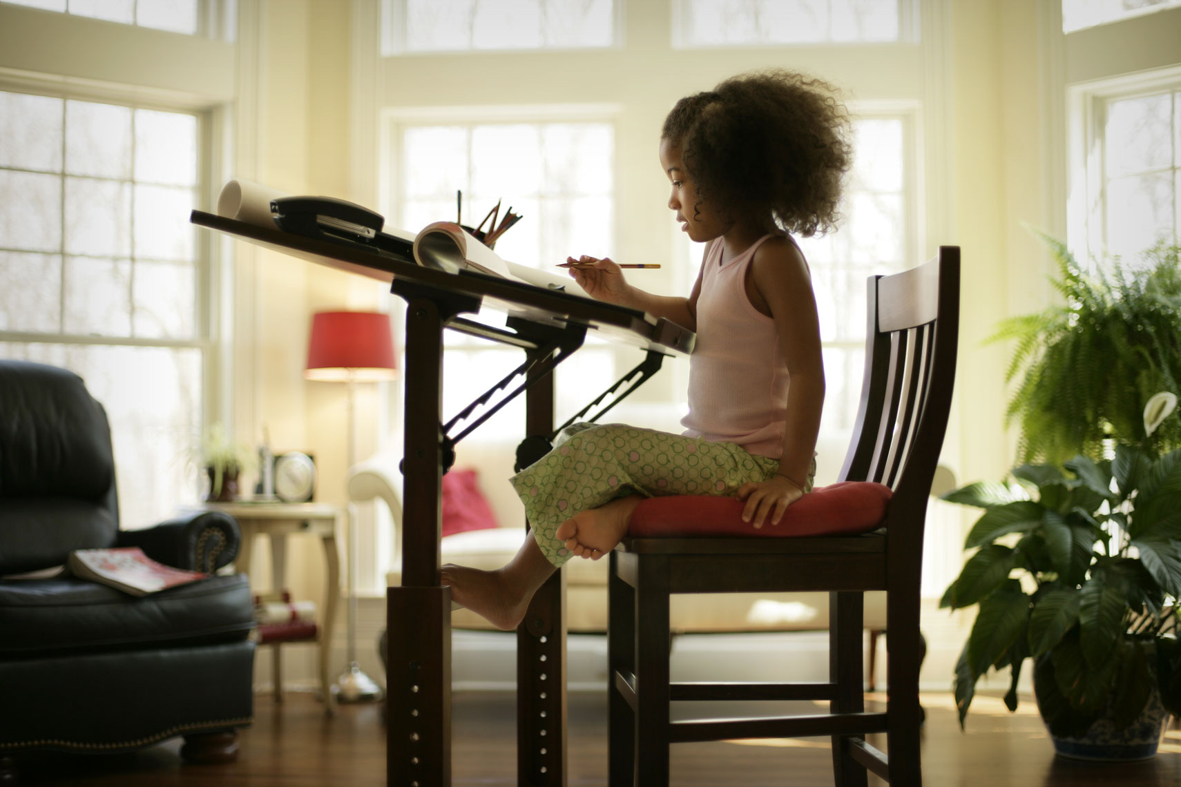 Environmental portrait of young African American girl at drafting table  for advertising use