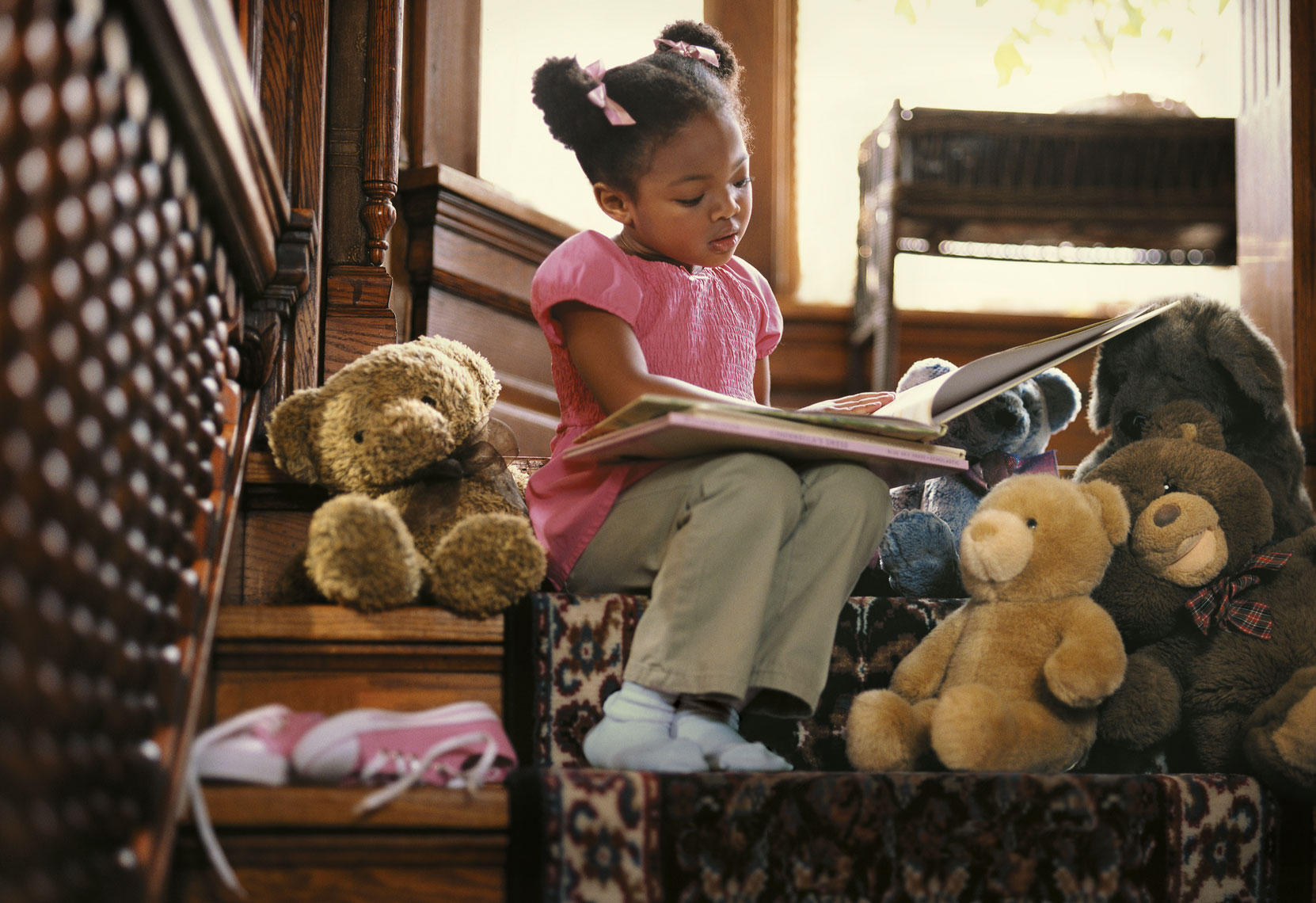 Environmental portrait of a young African American girl reading books for an advertising campaign