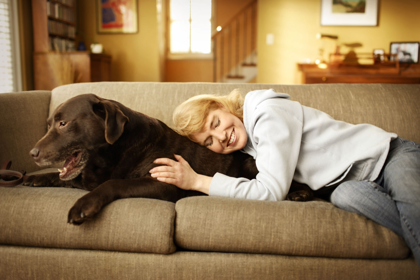 Lifestyle portrait of a woman with her dog on the couch