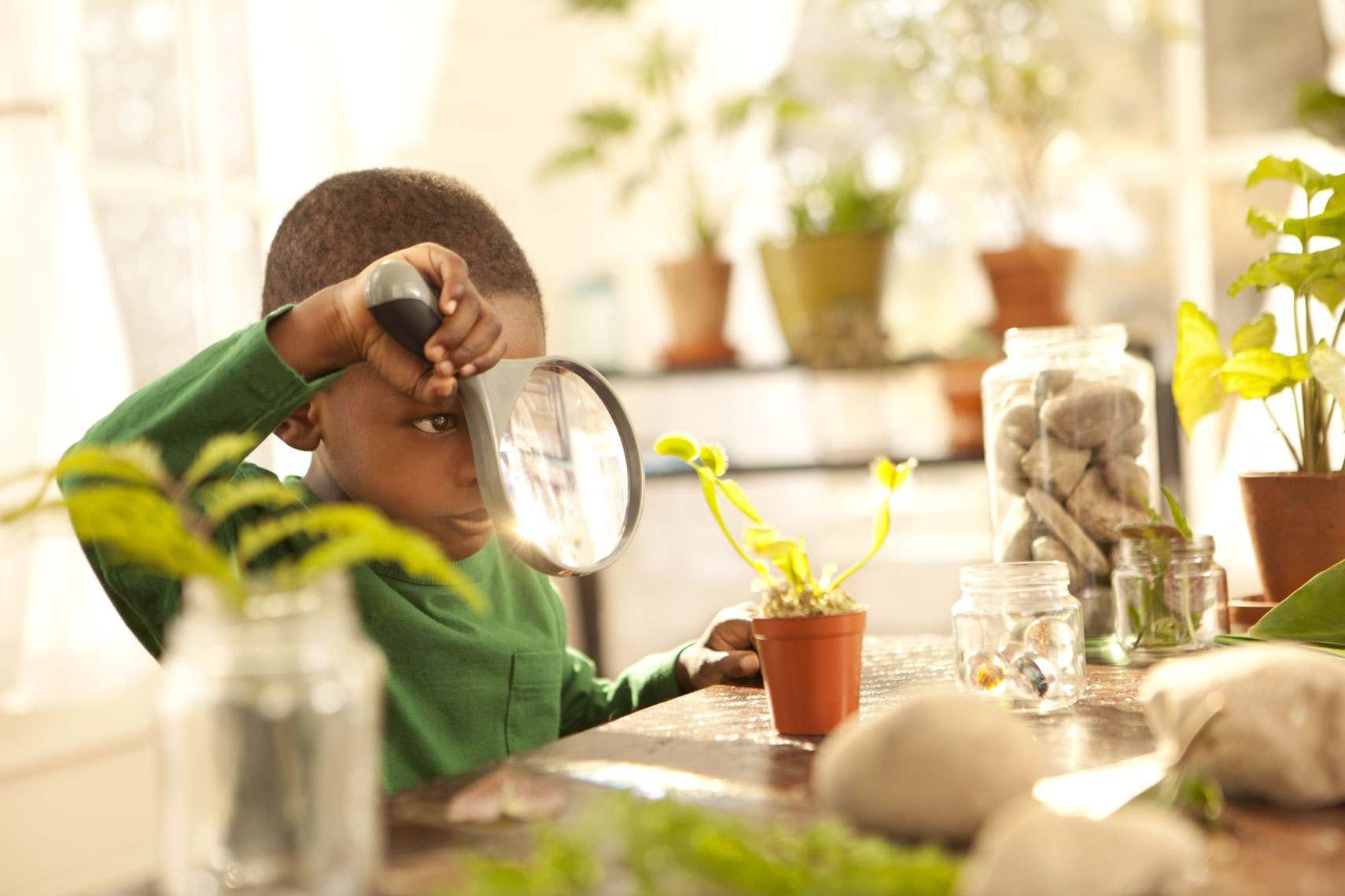 Lifestyle Portait Of African American Boy With Magnifying Glass