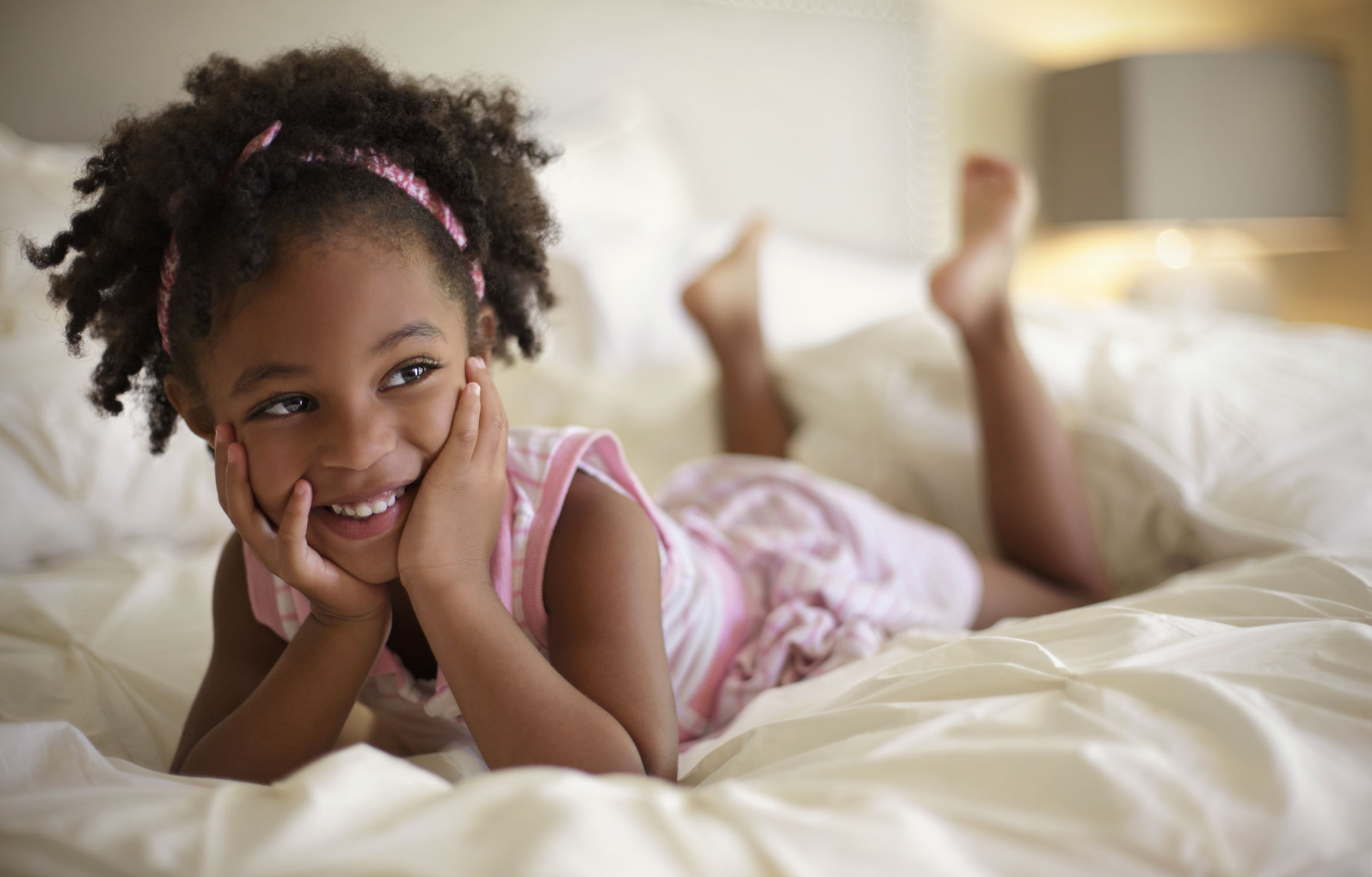 Environmental portrait of African American girl in bedroom