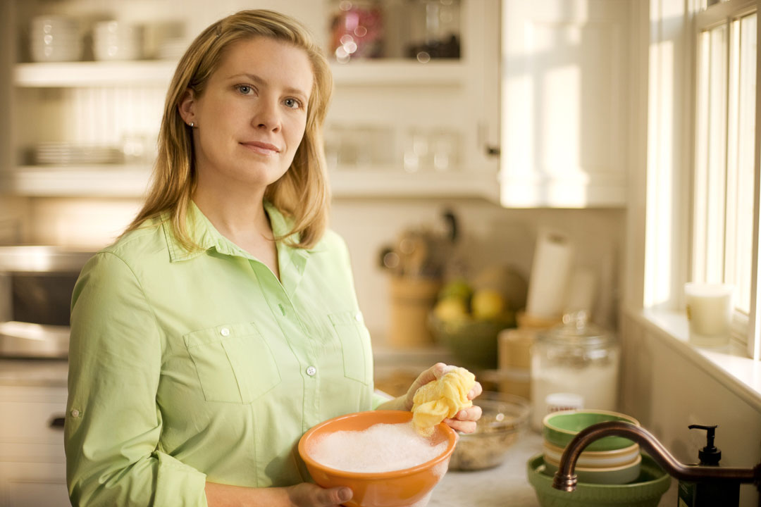 Environmental lifestyle portrait of woman doing dishes in kitchen